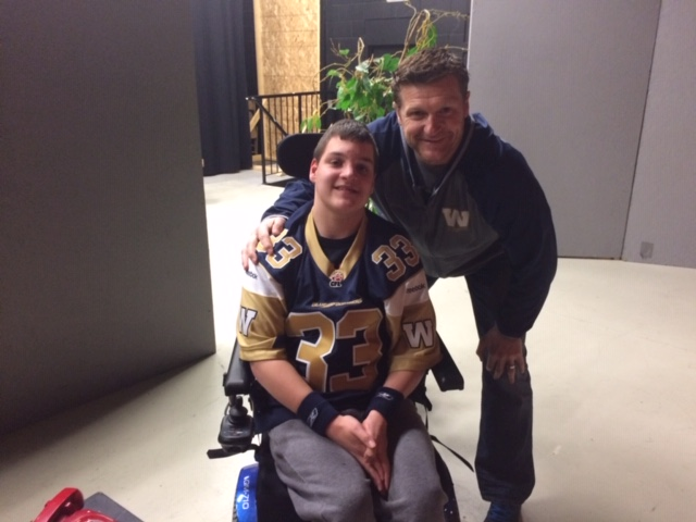 Jordan, in his wheelchair, meets Mike O'Shea, bending down