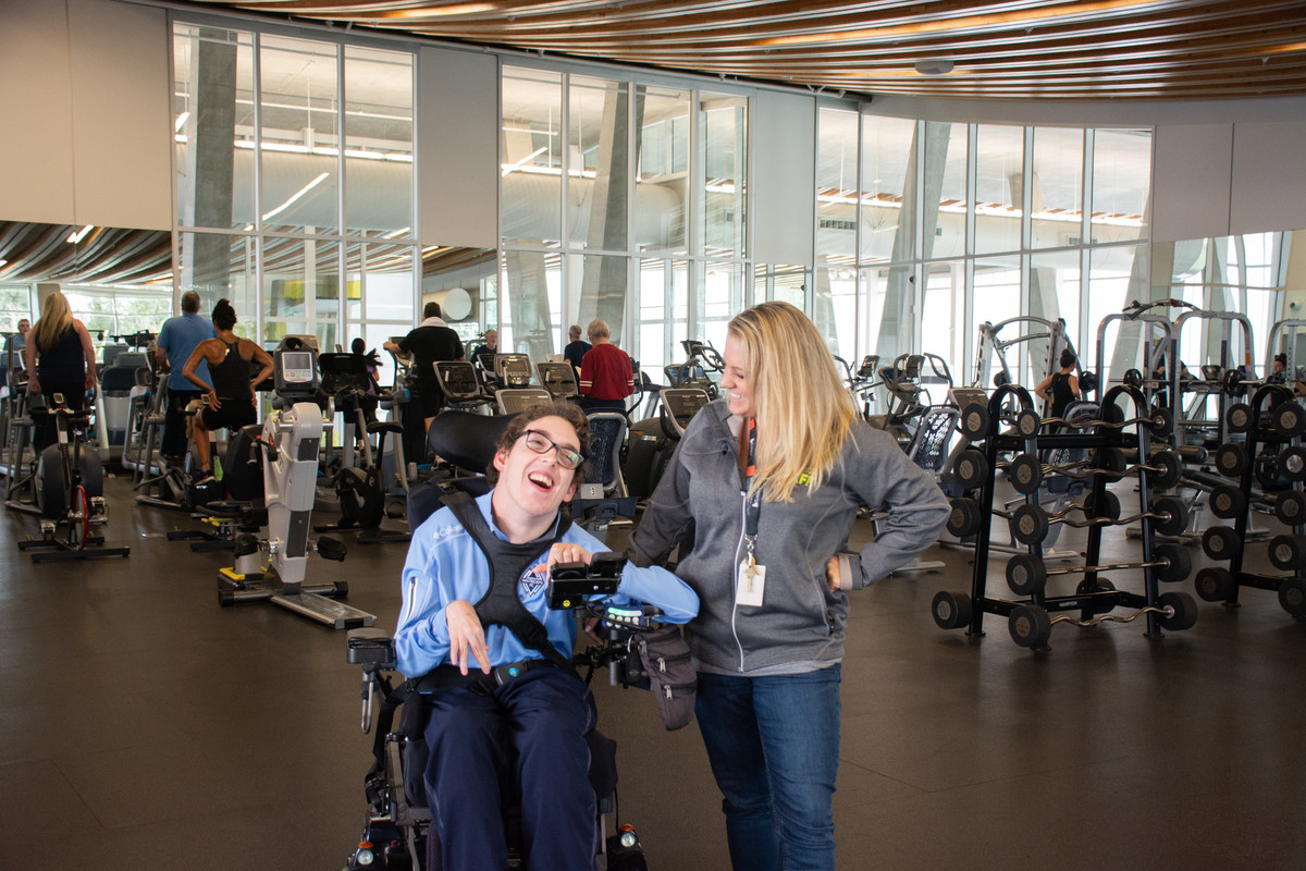 Nathan, a power wheelchair user is all smiles with city staff member at the accessible gym full of adaptive equipment.