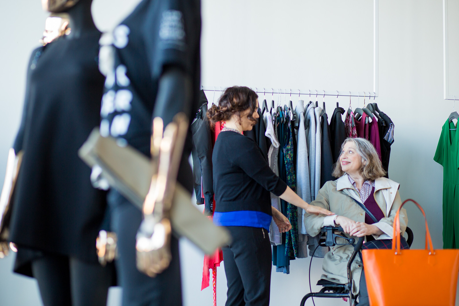 An elderly woman shops for a dress while using a wheeled mobility device. A saleswoman holds up a dress.