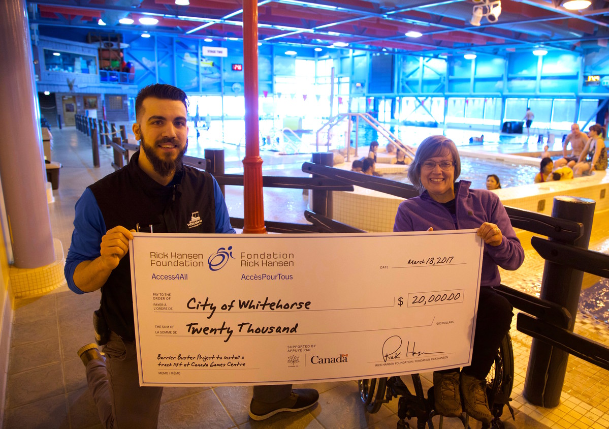 Woman using wheelchair presents cheque to pool