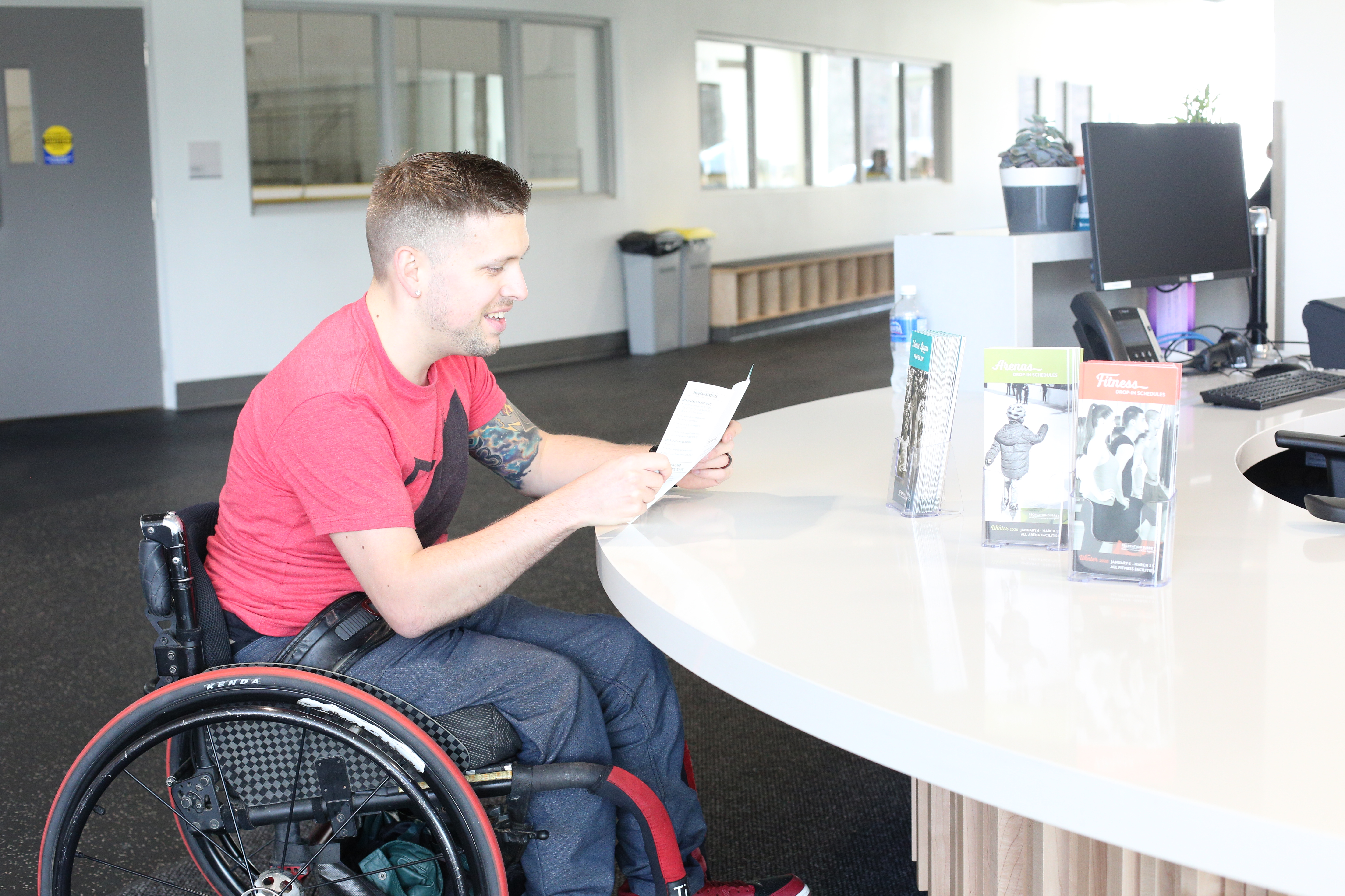 Wheelchair user Marco at universal height reception counter