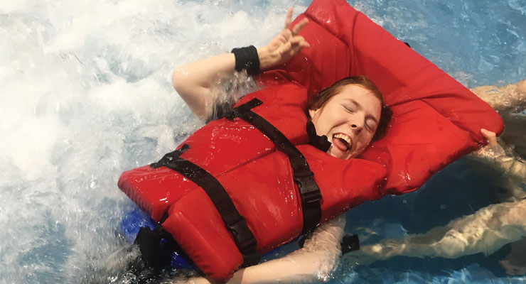 Girl wearing life jacket in pool, smiling