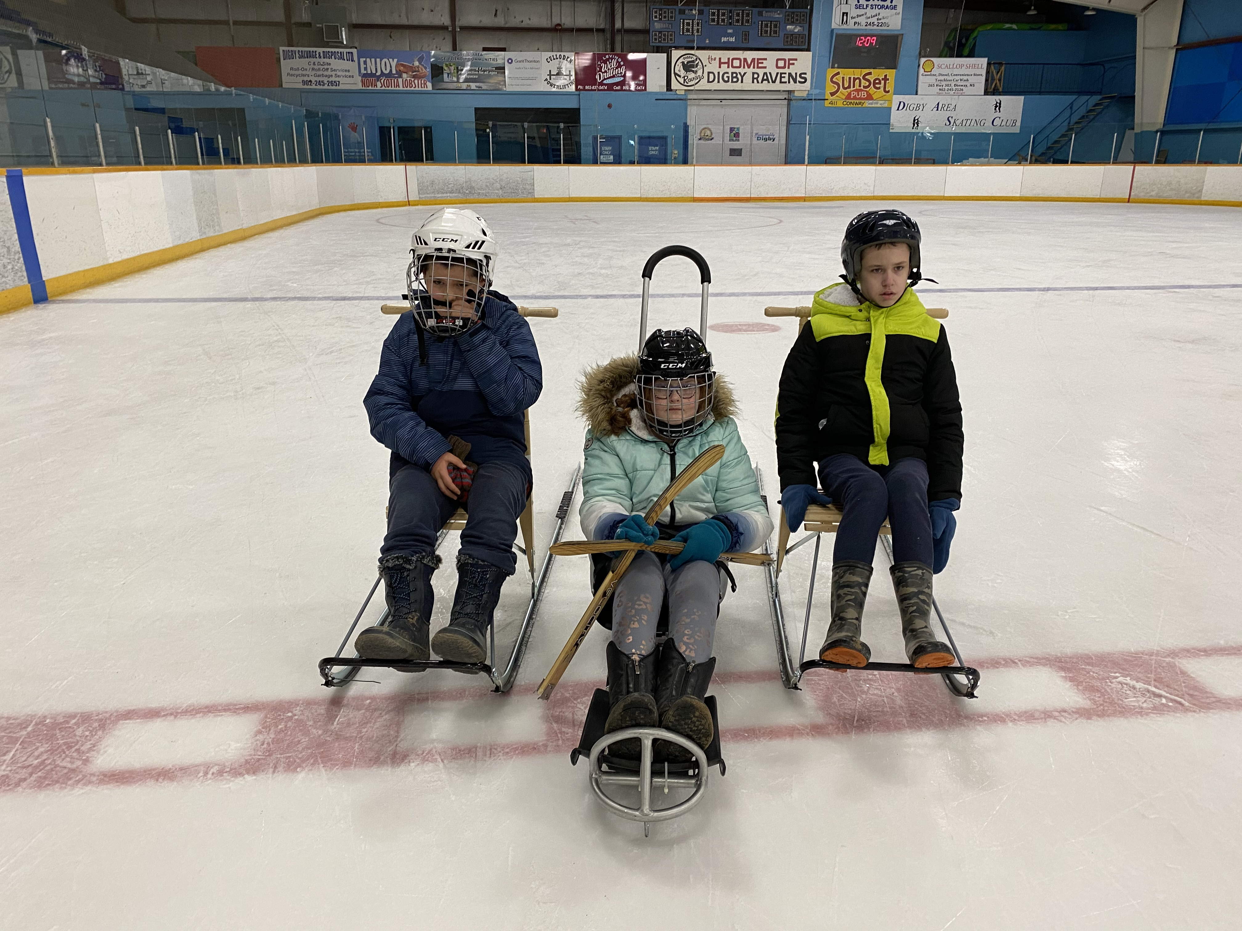 three people on ice rink