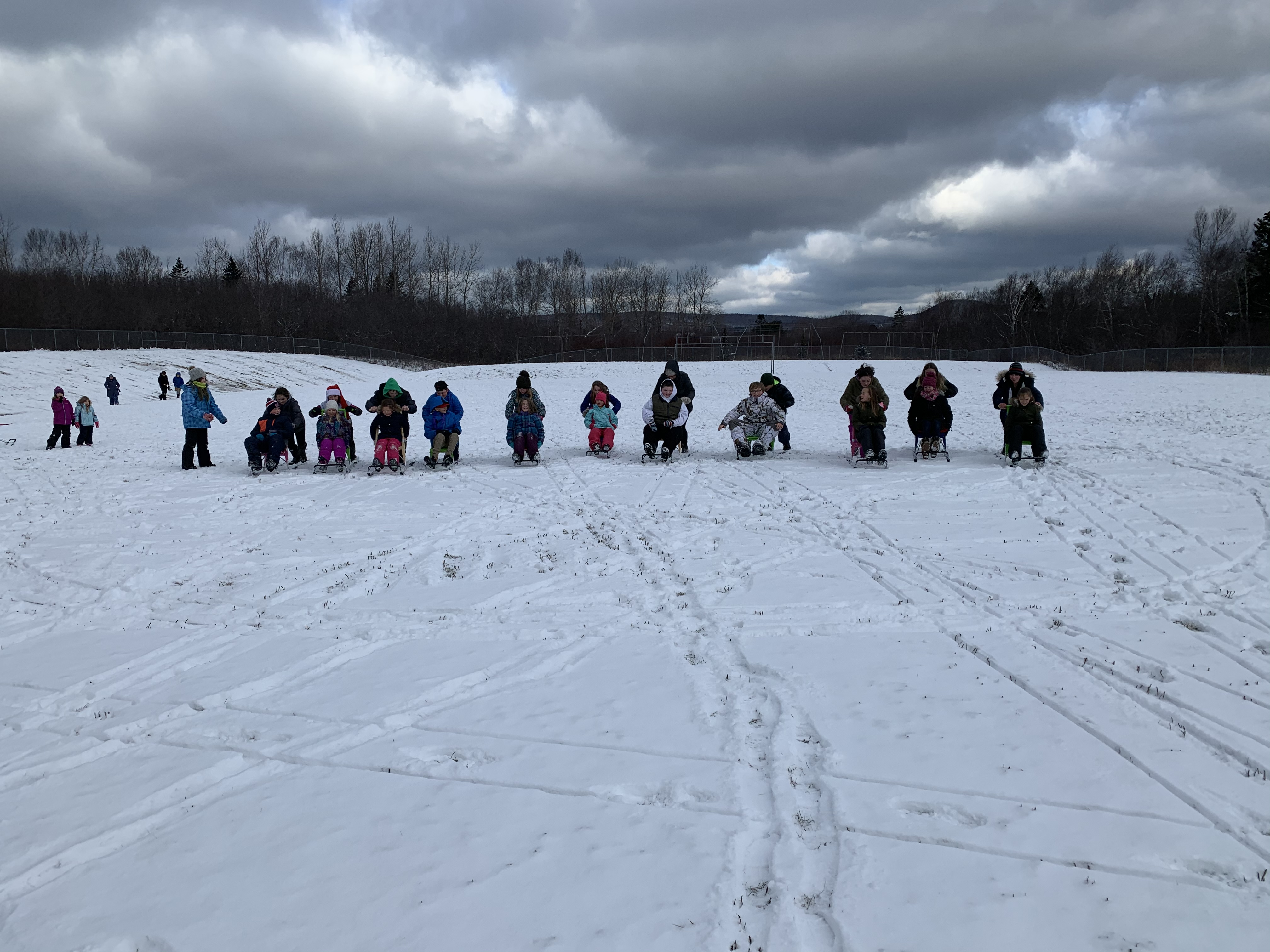 group using sleds on snow