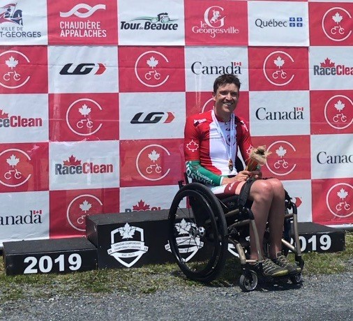 Matt in wheelchair, smiling, in front of red and white checkered backdrop