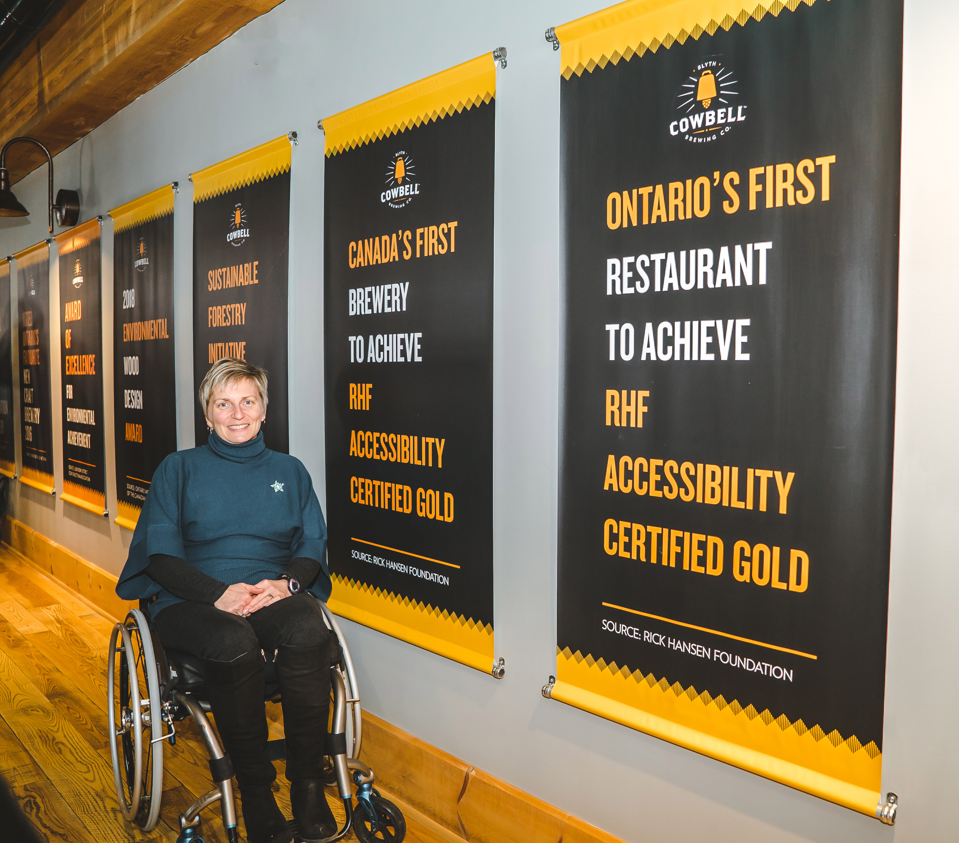 Julie, a woman using a wheelchair, smiles beside posters celebrating the Gold Accessibility Certification