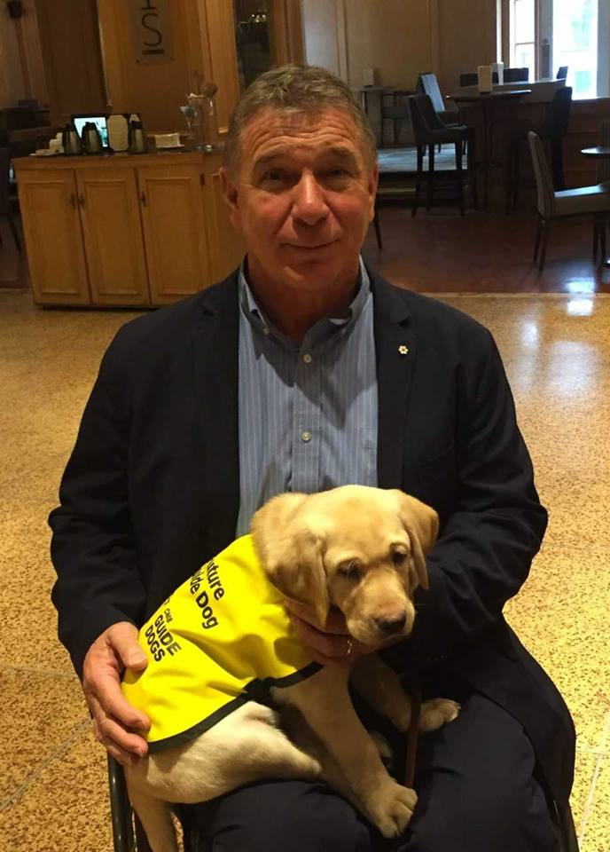 In a photograph from 2018, Rick Hansen holds a golden lab retriever puppy named Sherman. Sherman is now a working CNIB guide dog in Ontario!