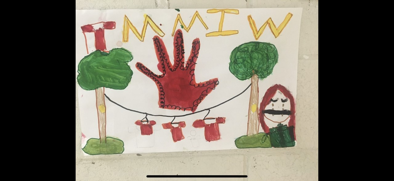 Milee's art says: TMMIW, and has red shirts hanging on a clothesline, and a woman crying in the foreground