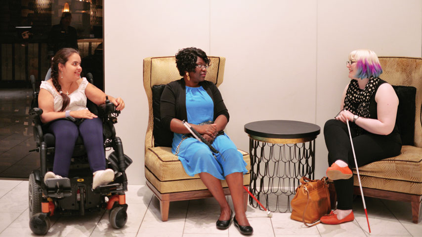 Three women with different disabilities chatting.