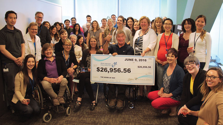 Rick and staff at the Rick Hansen Foundation with a cheque of $26,956.56