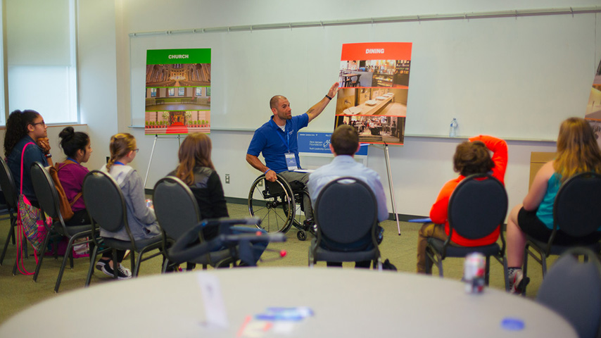 Man in wheelchair giving a talk to the audience.