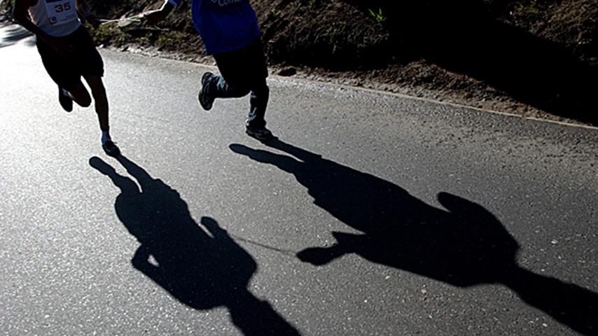 Two people running and their shadows are shown on the ground.