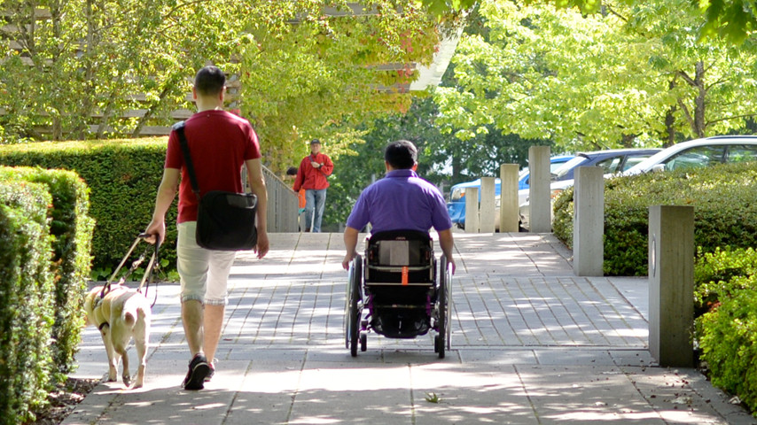 Two people with disabilities on an accessible path.