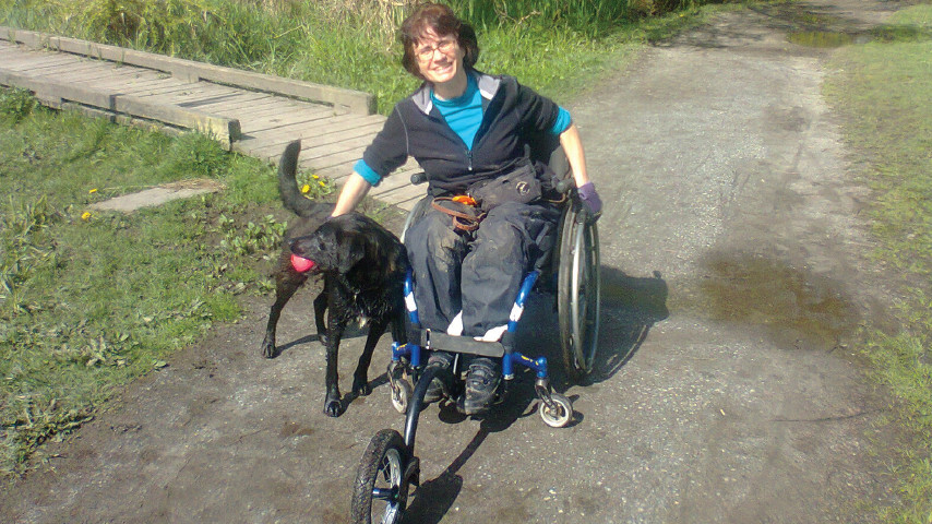 Luisa with her new FreeWheel attachment and a happy dog friend.