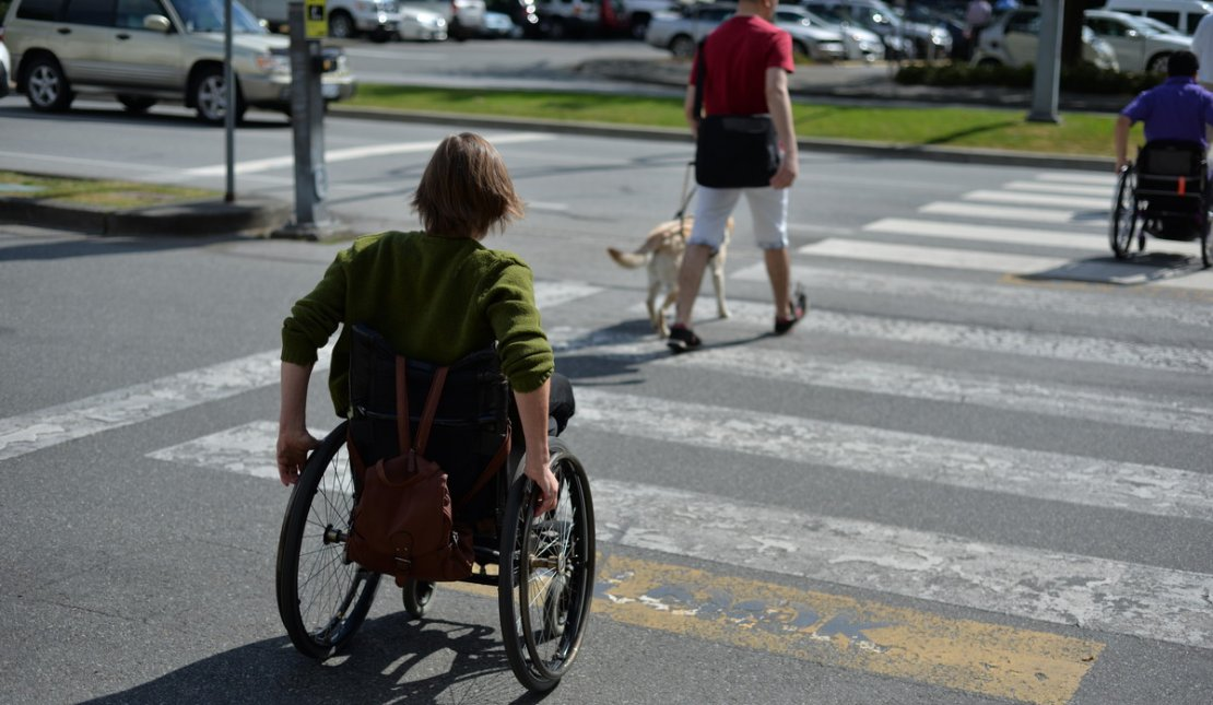 A woman uses a wheelchair while crossing a city street