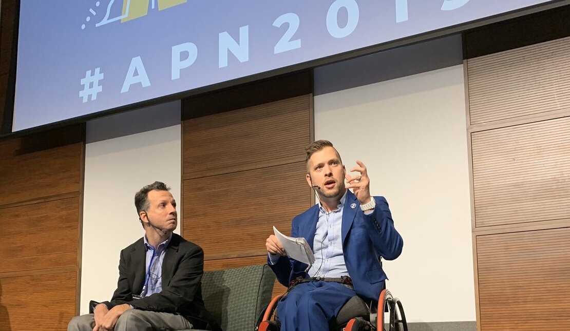 Marco Pasqua on stage using a wheelchair with a guest speaker