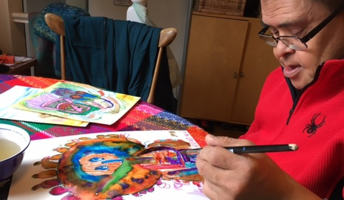 Daryl works on a colorful piece of artwork
