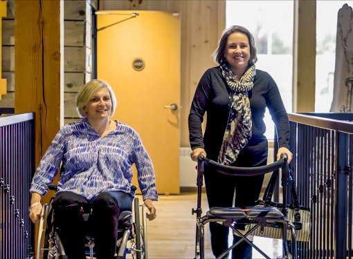 Two women smiling for camera. One uses a wheelchair and one uses a standing frame.