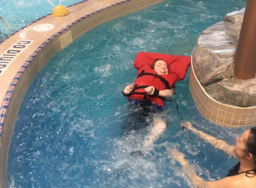 Eva at the pool,  floats in the lazy river wearing a life jacket