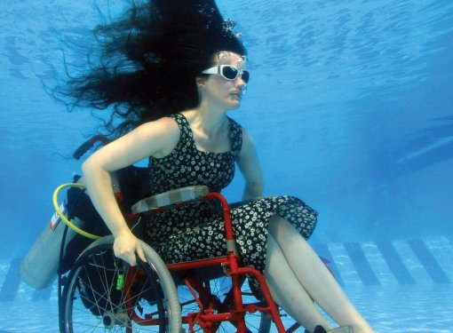 Woman in wheelchair underwater at bottom of pool with goggles