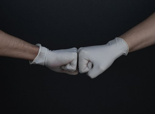 two fists wearing medical gloves