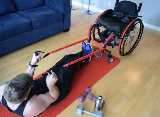 Marco on yoga mat pulling wheelchair using exercise bands