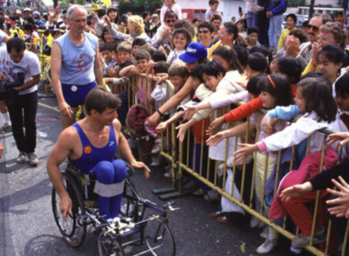 Rick Hansen on his wheelchair wheeling past youth supporters trying to high-five him during his Man In Motion World Tour.