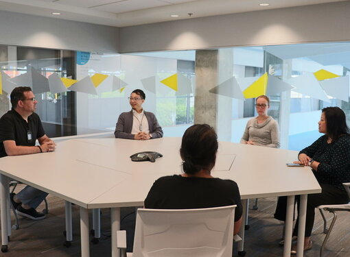 Wavefront CEO Christopher T. Sutton seated with a team of employees around a meeting table.