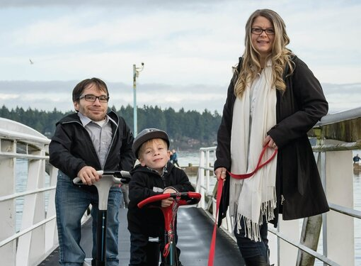 Jim, his wife and son on a dock using motorized scooters