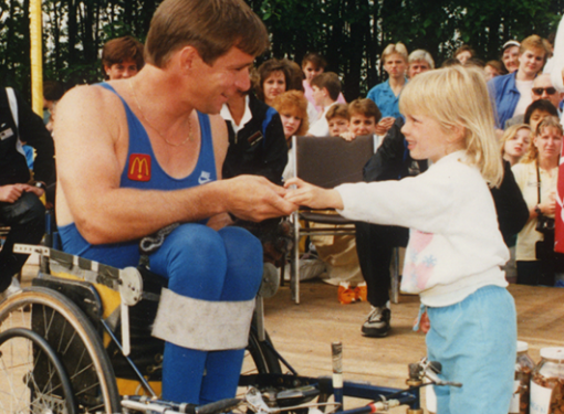 A little girl gives Rick Hansen a donation at a McDonald's restaurant during the Man in Motion World Tour