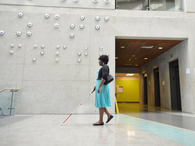 Woman in blue dress using probing cane walks in front of concrete wall with large braille