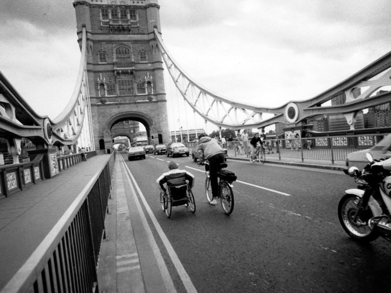 Rick Hansen wheeling over Tower Bridge, accompanied by Amanda Reid on bicycle.