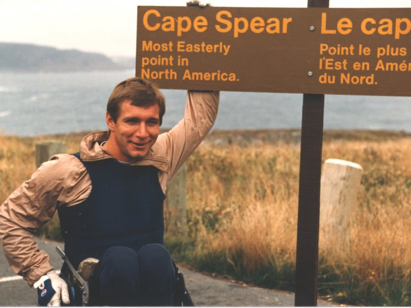"Rick Hansen by sign in Cape Spear ""Cape Spear's most easterly point in Canada"""