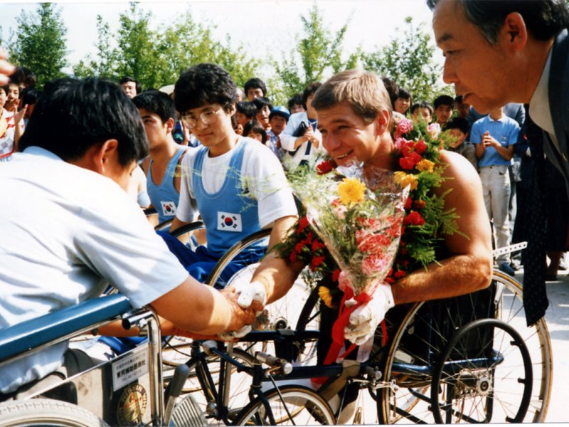 Rick Hansen receiving flowers and a wreath and meeting with a Korean wheelchair basketball team at the city hall of Daegu, Korea on May 7, 1986.