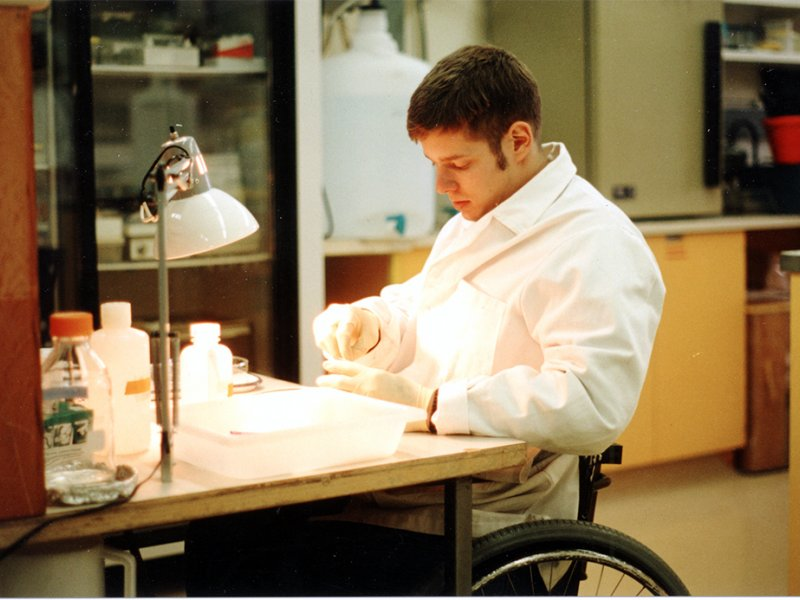 Man in a wheelchair conducting testing in a labratory