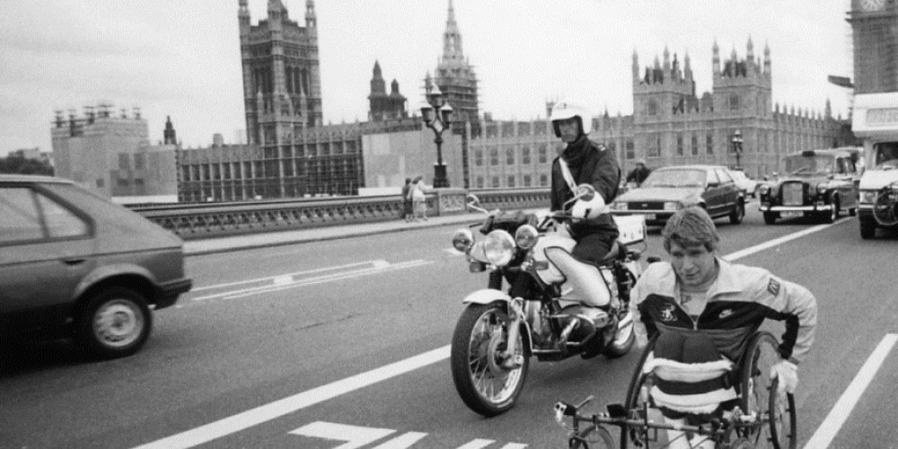 Rick Hansen wheeling past Big Ben alongside Amanda Reid, with a police escort in London, England during the world tour.