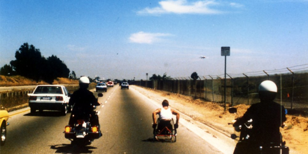 Rick Hansen with a police escort while wheeling in Florida in 1985.