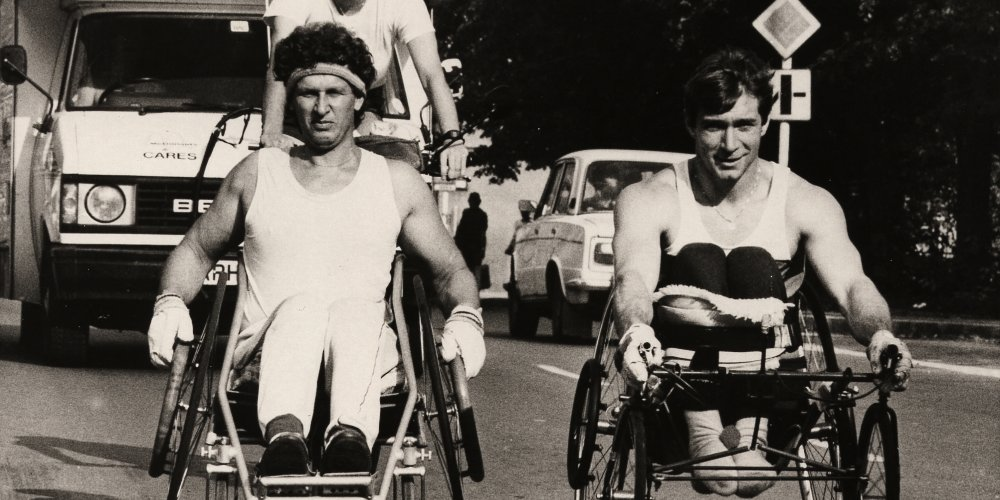 Rick Hansen wheeling in Czechoslovakia with another wheelchair athlete, accompanied by Amanda Reid following behind on a bicycle.