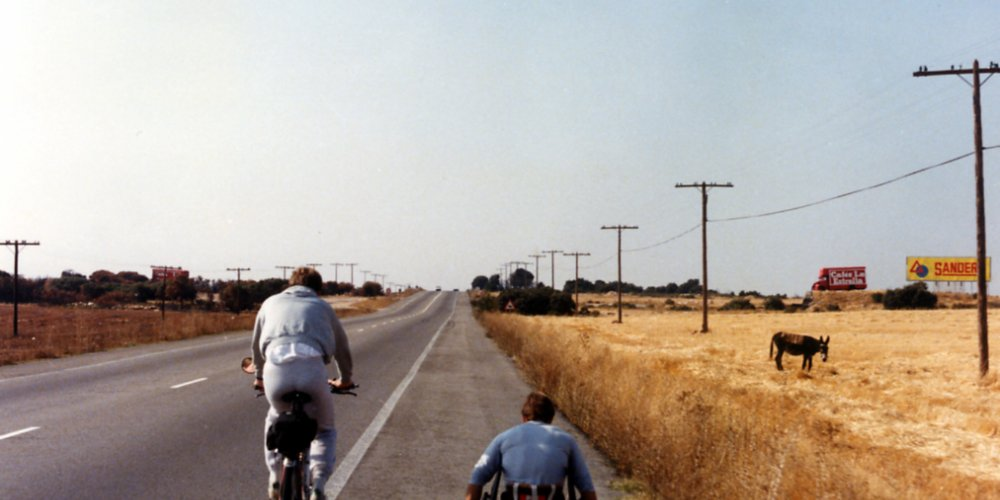 Rick Hansen wheeling through the Spanish countryside, accompanied by Amanda Reid on bicycle.