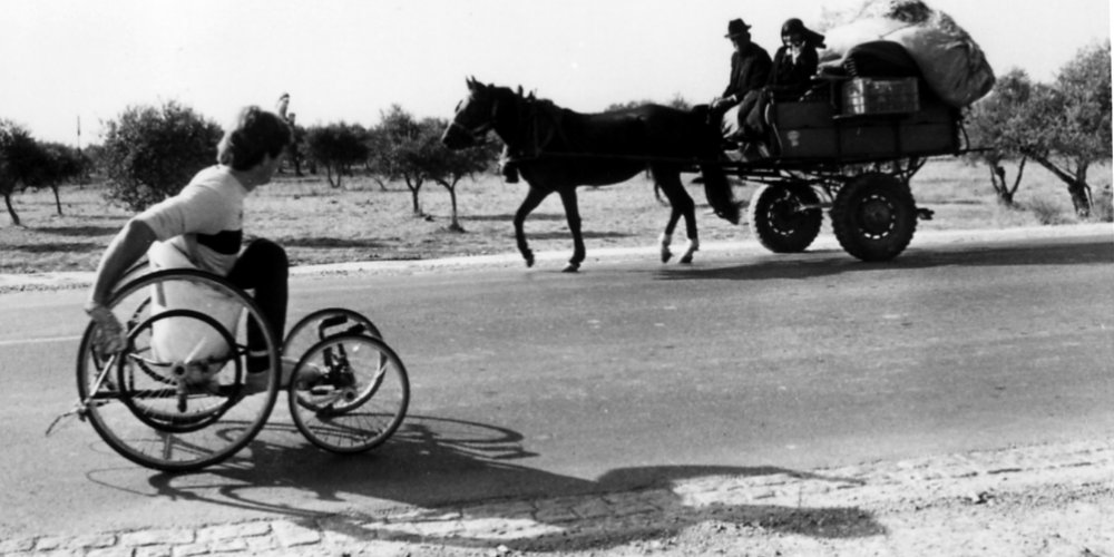 Rick Hansen wheels past locals in a horse and buggy in rural Portugal during early November of 1985.