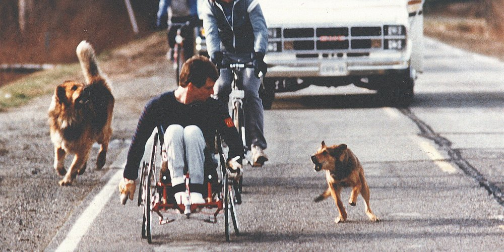 Rick Hansen being chased by dogs during the start of the World Tour in Washington State.