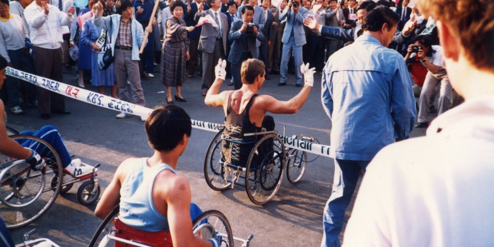 Rick Hansen going through a banner with Korean Broadcasting KBS on it
