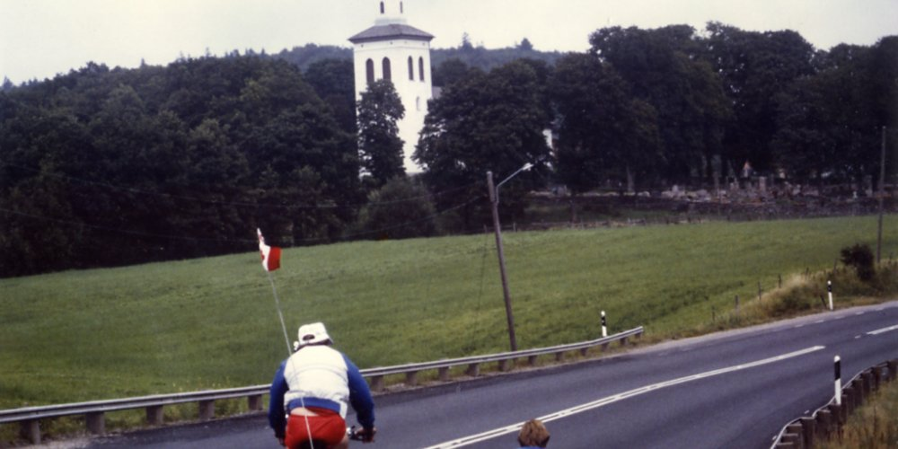 Rick Hansen wheeling towards a chapel accompanied by Lee Gibson, in Sweden during August of 1985.