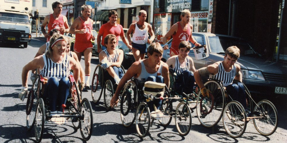 Rick Hansen in Adelaide, Australia accompanied by several other people in wheelchairs.